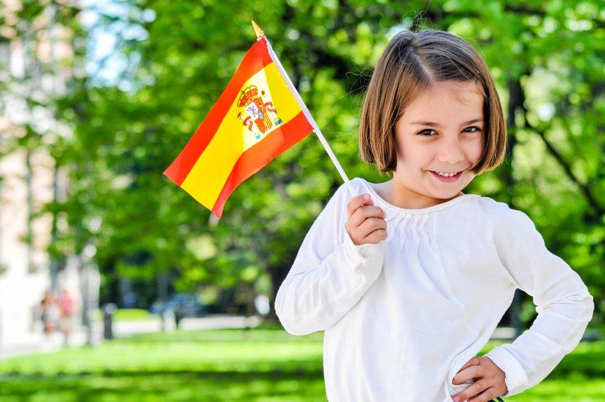 Hiszpański dla dzieci w Baby English Center - dziewczynka w parku z flagą Hiszpanii