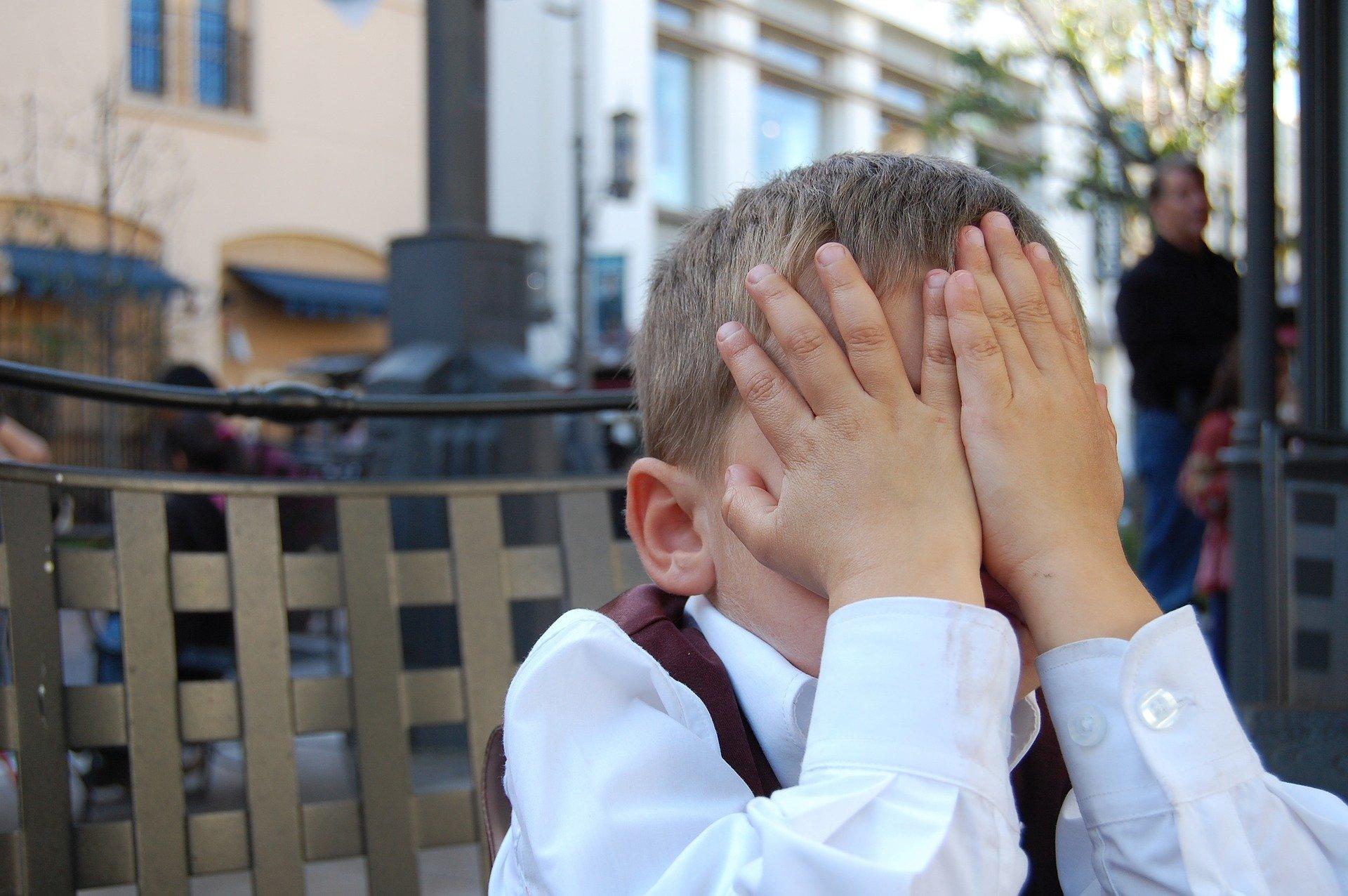 chłopiec zakrywający twarz