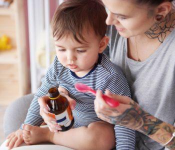 Close up of toddler taking medicine
