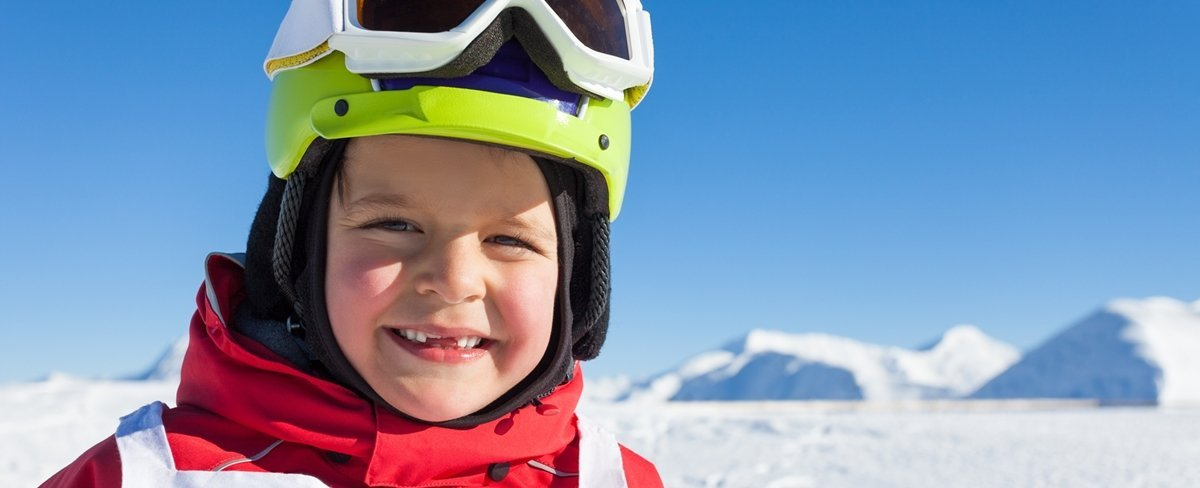 Happy little skier in safety helmet and goggles
