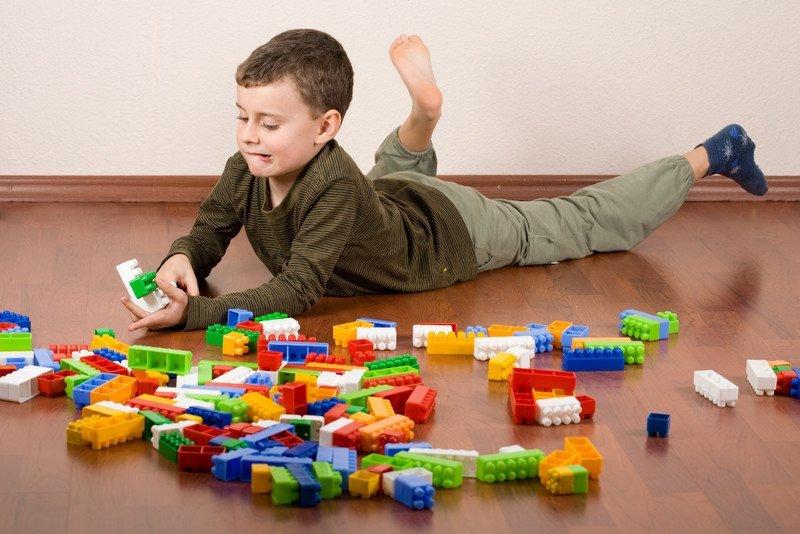 chłopiec 8 lat bawi sie klockami na podłodze