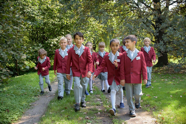 dzieci w mundurkach spacerujące po parku