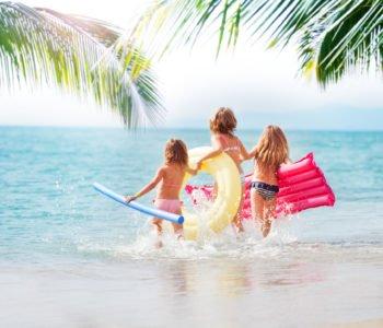 trzy dziewczynki biegnące w wodzie na tropikalnej plaży
