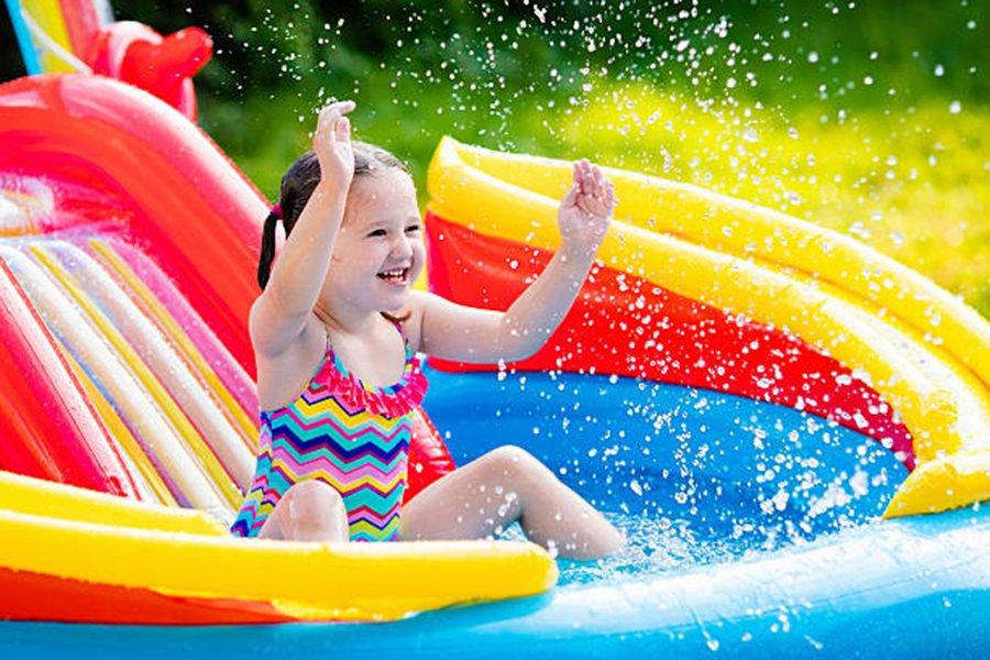 Dziewczynka bawi się w basenie dmuchanym z wodą