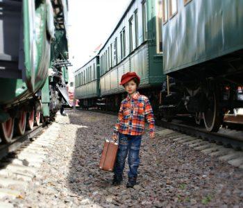 Chłopiec z walizką stojący obok pociągów
