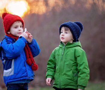 Portrait of two adorable boys, brothers, on a winter day, sunset
