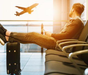 Mężczyzna siedzi z nogami na walizce i patrzy na odlatujący samolot