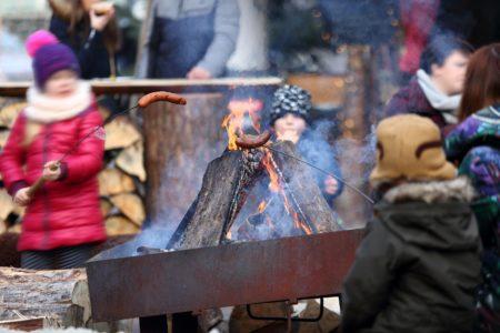 Dzieci pieką kiełbaski nad ogniskiem.