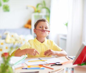 szczęśliwy chłopiec odrabiający pracę domową