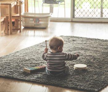 Dziecko na dywanie gra na bębenku