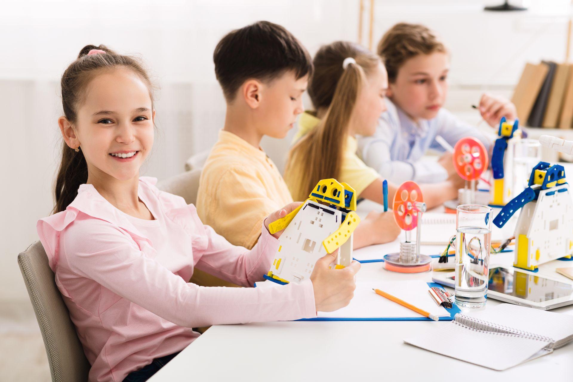 Dzieci na zajęciach plastycznych tworzą papierowe roboty