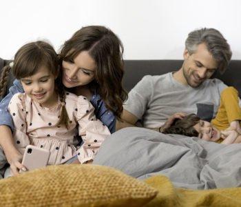 uśmiechnięta rodzina leży w łózku