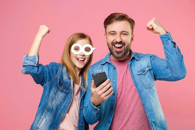 Uśmiechnięta dziewczynka z tatą, który trzyma telefon komórkowy w ręce