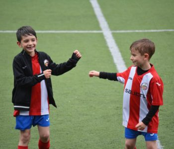 chłopcy w strojach piłkarskich uśmiechają się