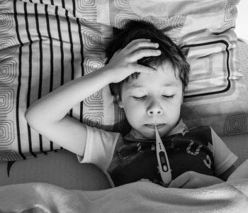 Choy chłopiec leżący w łóżku z termometrem