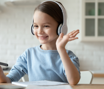 uśmiechnięta dziewczynka siedzi w słuchawkach przed komputerem