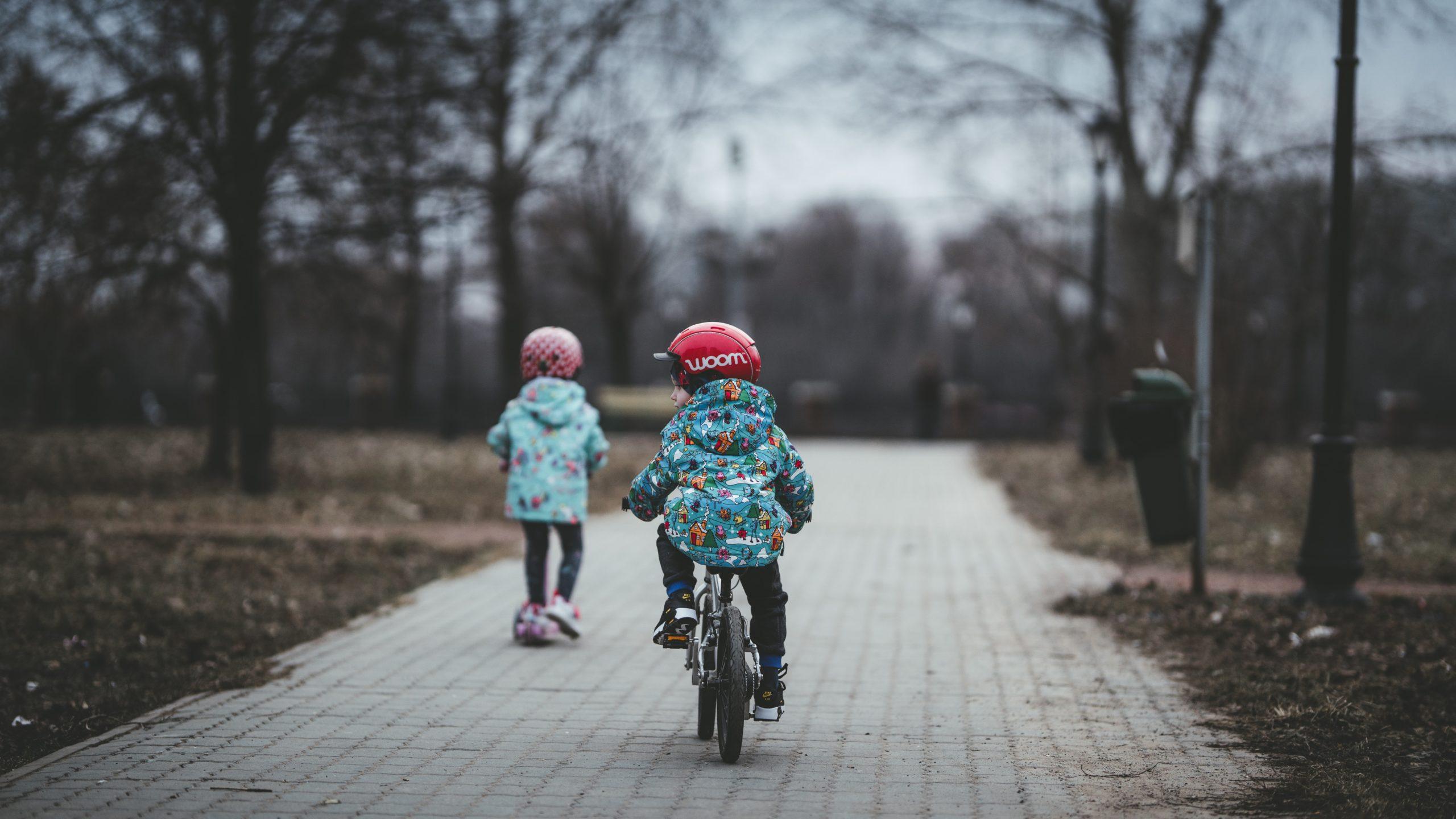 dzieci jadą na rowerch w kaskach