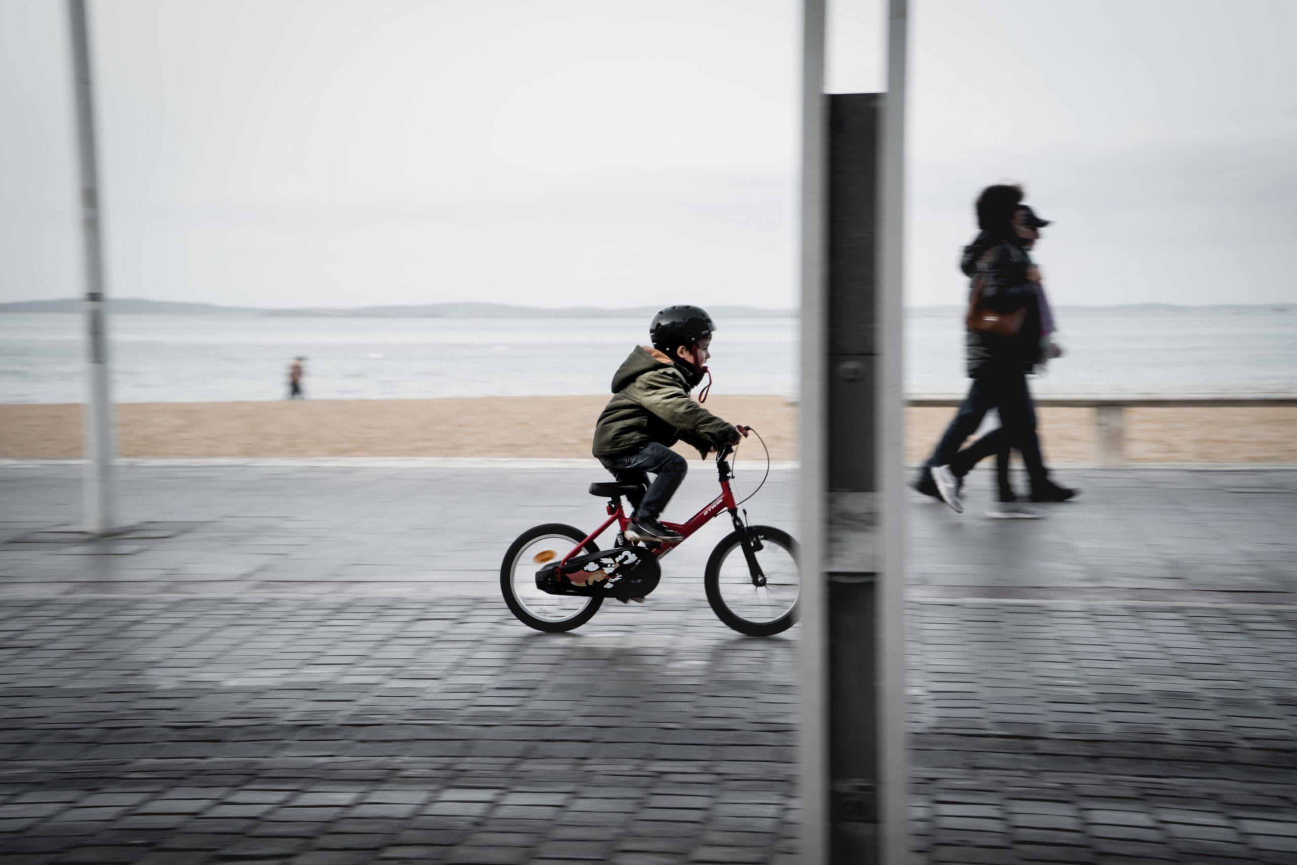 chłopiec w kasku jedzie na rowerze