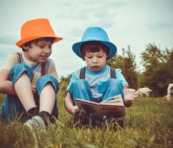 dwóch chłopców czyta książkę