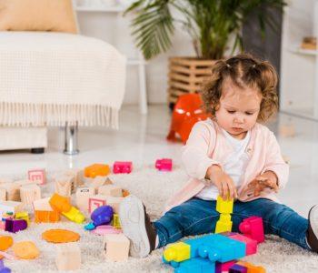 Dziecko bawki się klockami na podłodze