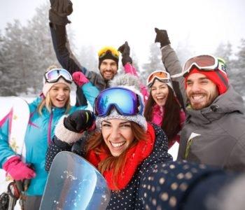 uśmiechnięci ludzie z nartami