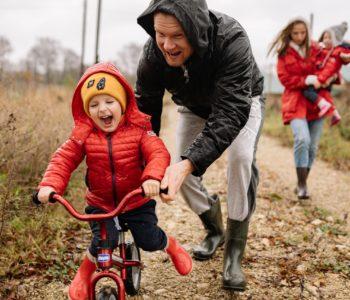 dziecko z tatą uczy się jeździć na rowerze