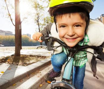 uśmiechnięty chłopiec w żółtym kasku jedzie na rowerze