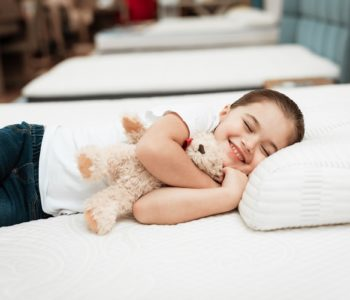 Uśmiechnięta dziewczynka z misiem leży na materacu i poduszcze w sklepie meblowym