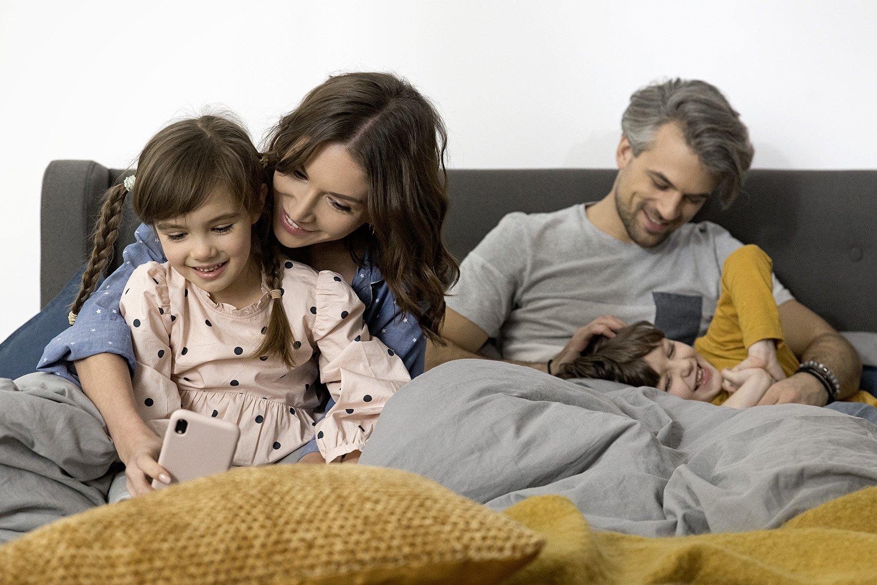Mama z córką patrzą w smarfona a tata bawi sie z synem na sofie