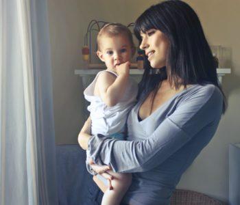 Uśmiechnięta mama trzyma dziecko na rękach