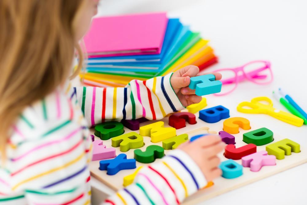 Dziewczynka układa literki według kolejności w alfabecie