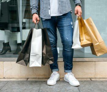Mężczyzna w jeansach z torbami na zakupy
