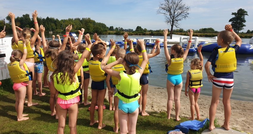 grupa dzieci na kąpielisku nad jeziorem