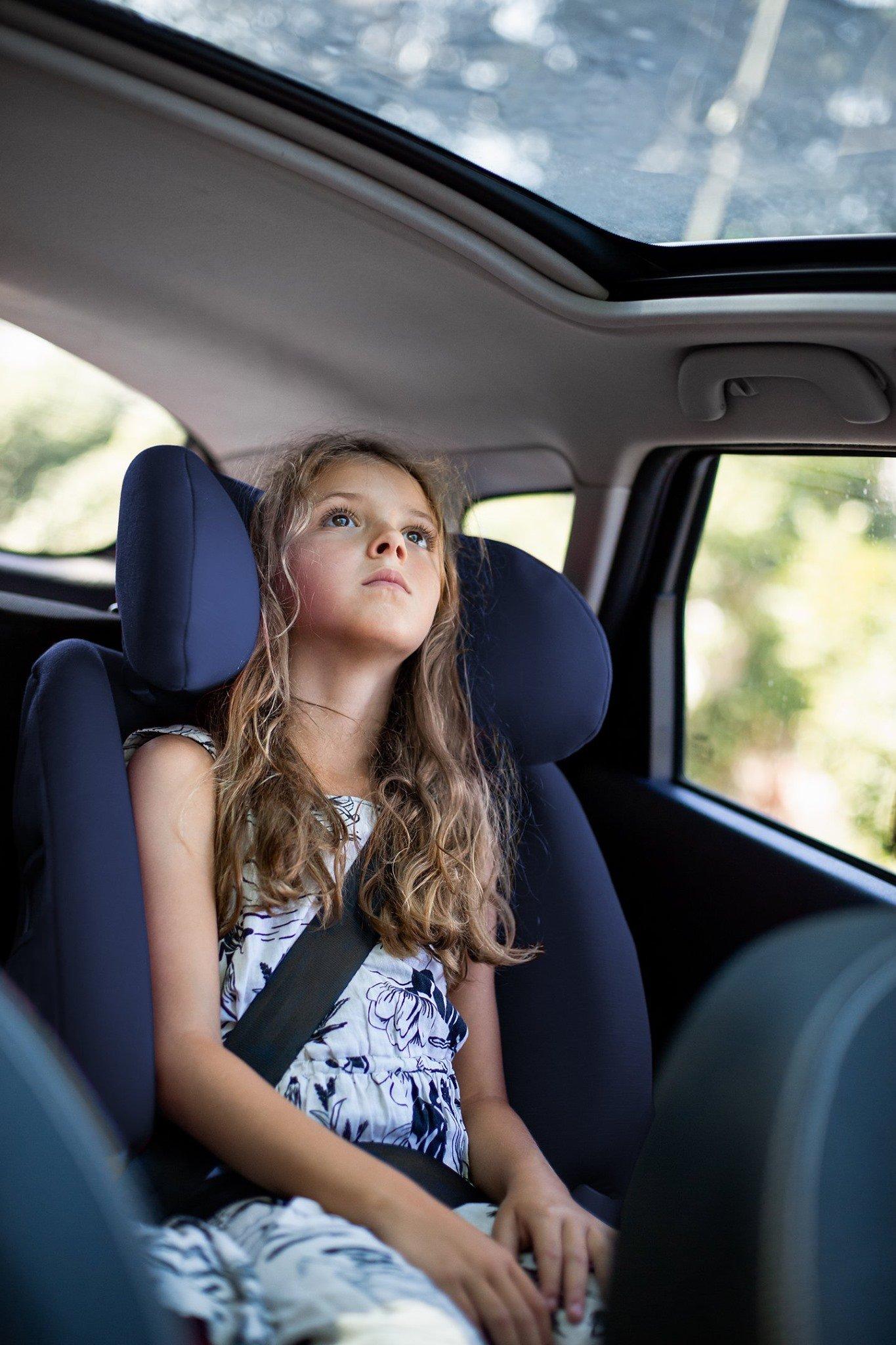 Dziewczynka w sukience siedzi w foteliku samochodowym