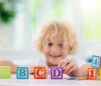 Dziecko uczy się liter za pomoca drewnianych klocków