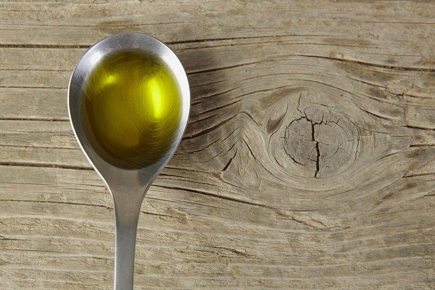 łyżeczka z oliwą na drewniany stole