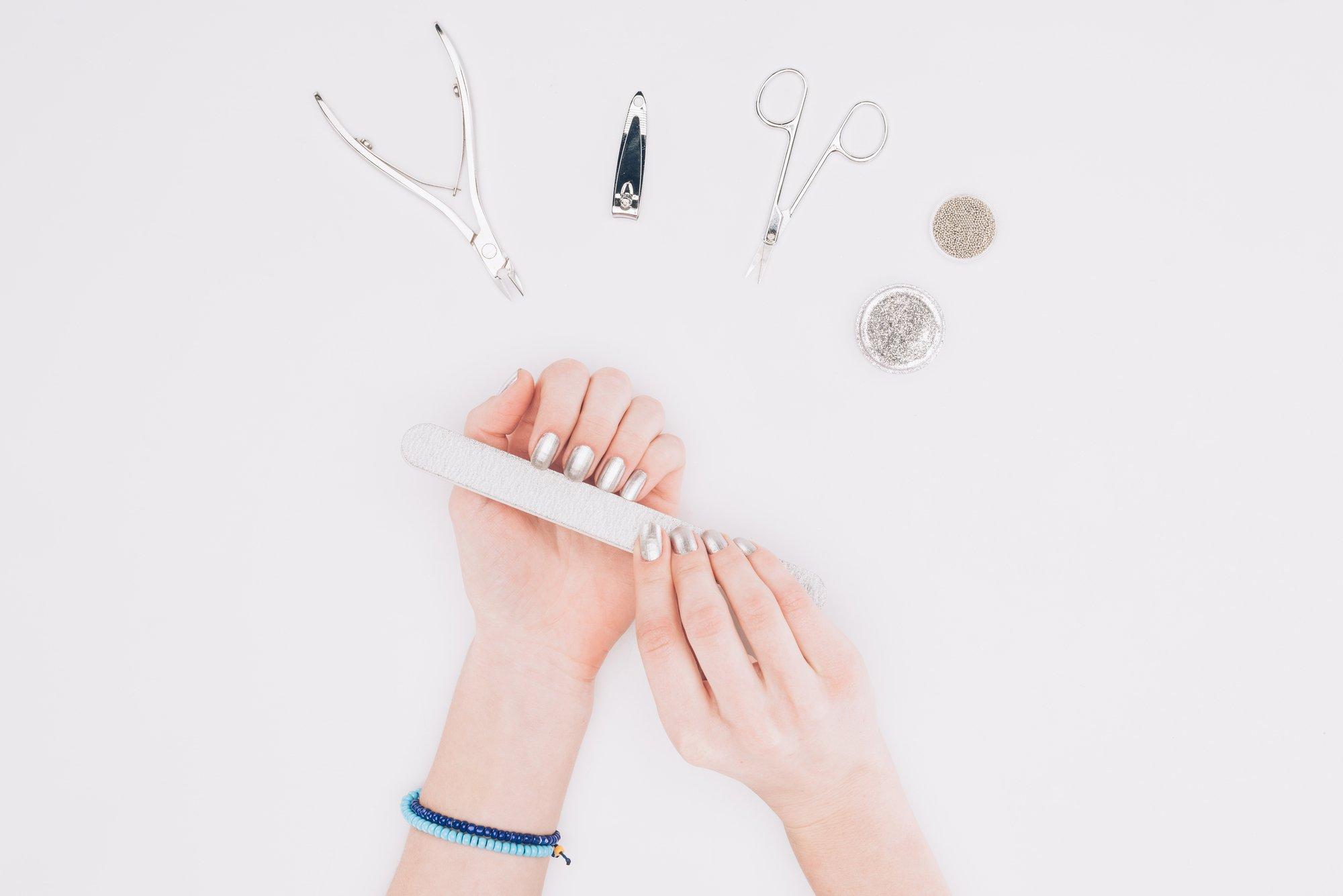 kobieta piłuje pilniczkiem paznokcie , na górze są widoczne przyżady do minicure