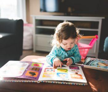 Dziecko ogłada księżeczkę z obrazkami