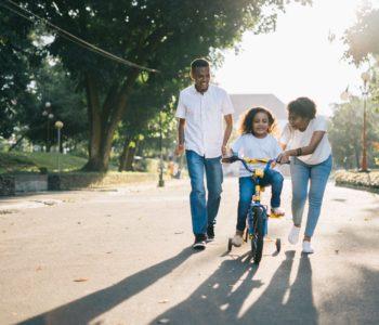 Mama i tata pomagająa jechać dziewczynce na rowerze