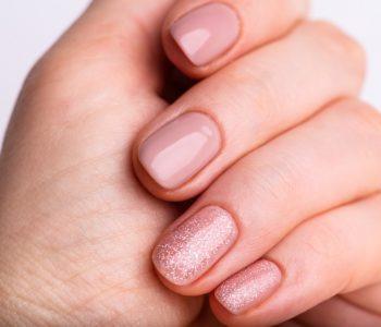 paznokcie pomalowane na cielisty kolor i z brokatem