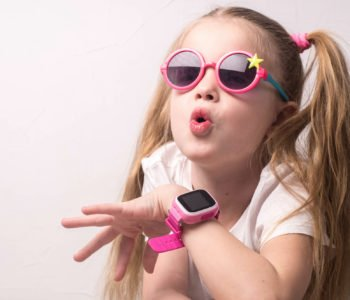 Technology for children: a girl wearing pink glasses uses a smartwatch.