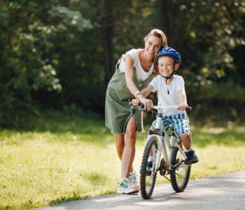 mama uczy jeździć chłopca na rowerze