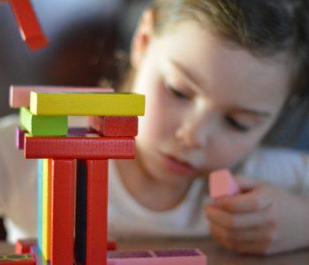 dziewczynka układa wieżę z klockó drewnianych