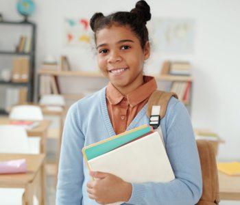 uśmiechnięta dziewczynka stoi z książką w eku