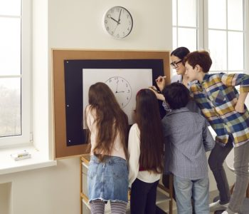nauczycielka uczy dzieci odczytywania godzin na zegarze