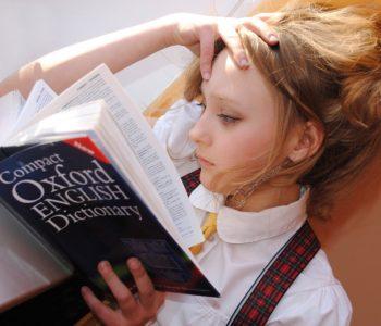 dziewczynka czyta słownik do języka angielskiego Oxford