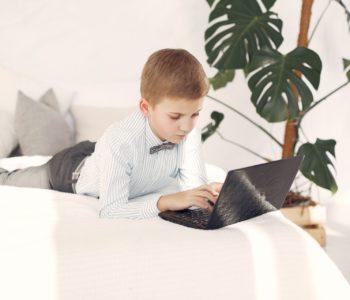 chłopiec leży na łózku i poisze w laptopie