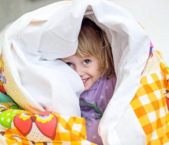 chłopiec zakrywa się kocem