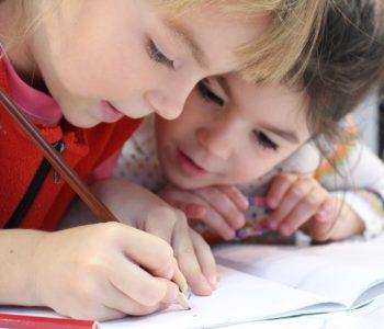 dziewczynka pisze w zeszycie a druga się przygląda