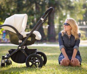 kobieta siedzi na trawie a obok niej stoi wózek z dzieckiem